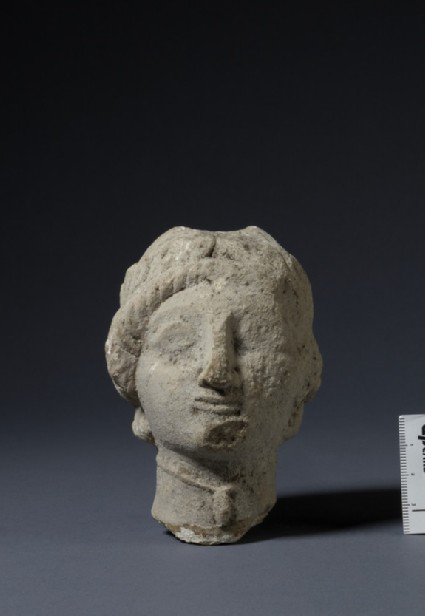 Limestone head of female votary with sakkos and wreath of leaves, fragment of votive-statuette