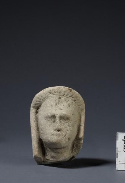 Limestone head of female votary, veiled, fragment of votive statuette