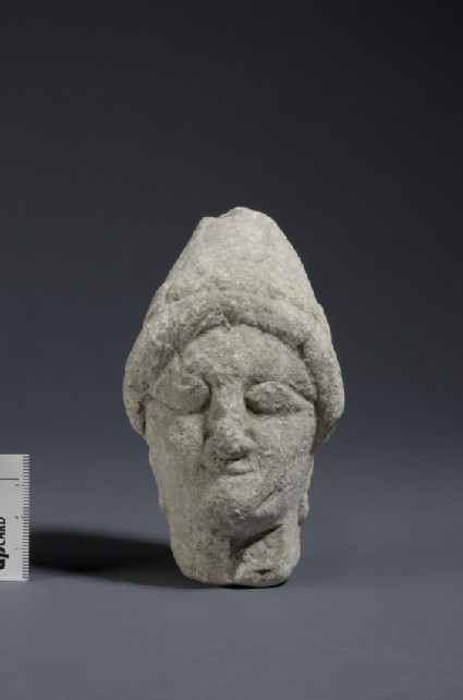 Limestone head of female votary with sakkos and rosette earrings, fragment of votive-statuette