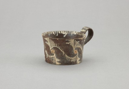 Kamares ware one-handled cup. Decorated with white painted curvilinear designs on black slip