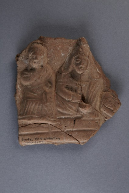 Fragment of ceramic plaque, two figures in relief: on the right, a beardless man in Phrygian attire, on the left, a woman