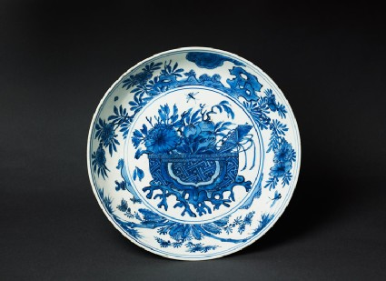 Blue-and-white dish with basket of flowers