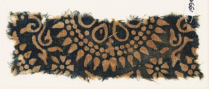 Textile fragment with part of a large rosette, surrounded by dots and petals