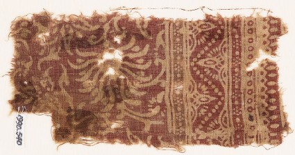 Textile fragment with swirling flower-heads and a dotted zigzag
