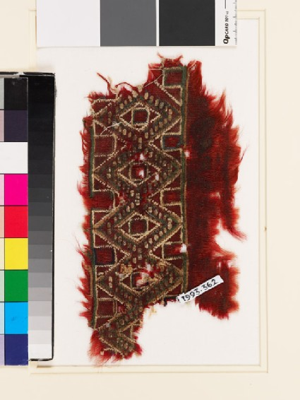 Textile fragment with band of linked diamond-shapes and squares