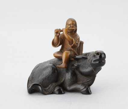 Netsuke in the form of Ōshikyō sitting on an ox playing the flute