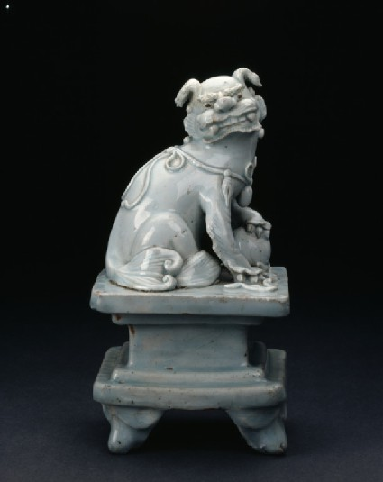 Lion dog with ball on a pedestal