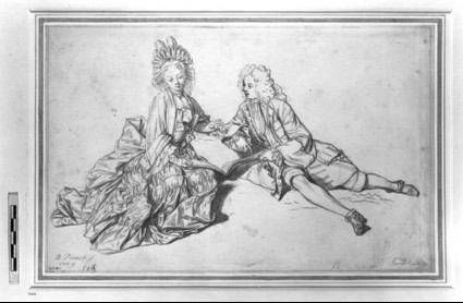 A man and a woman seated on the ground, sharing a book of music