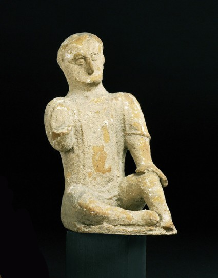 Seated figure of young boy, temple boy, terracotta or limestone