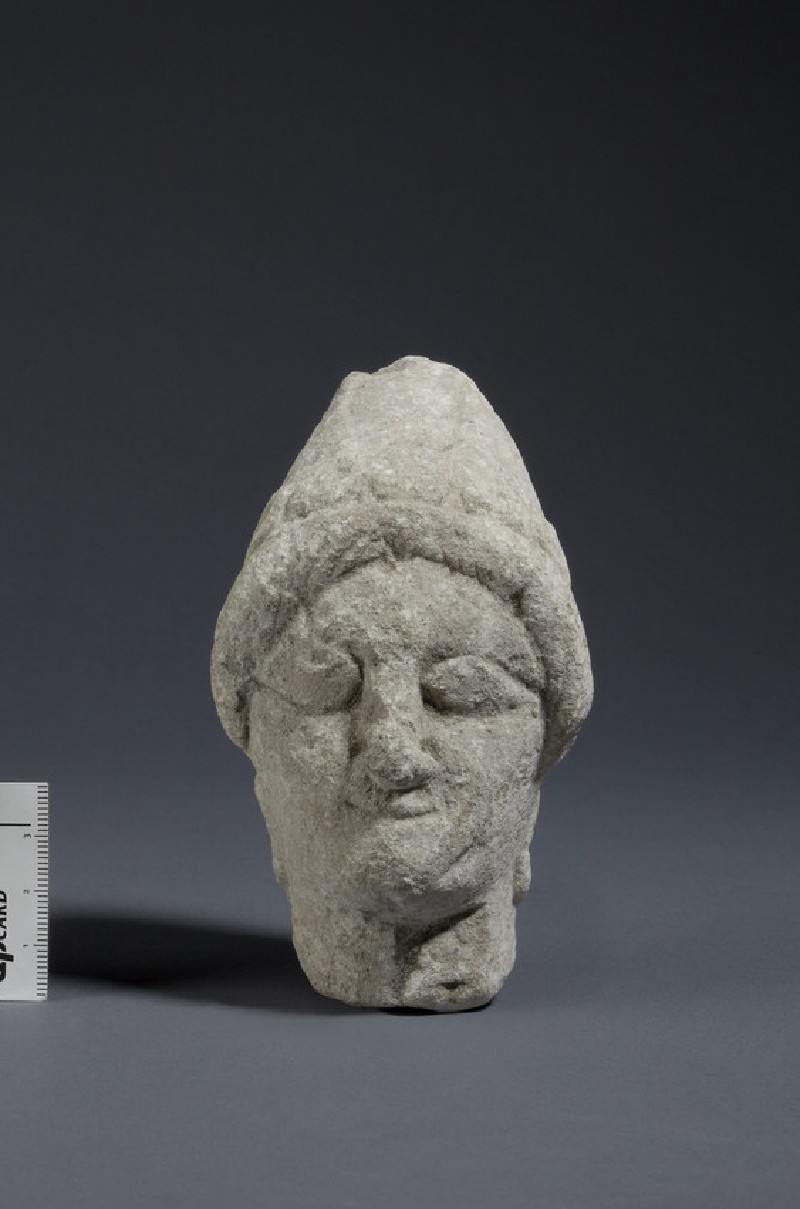 Limestone head of female votary with sakkos and rosette earrings, fragment of votive-statuette (AN1874.348)