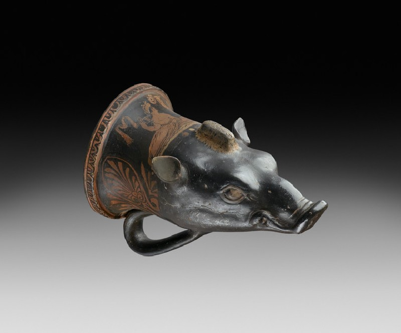 Apulian red-figure pottery rhyton shaped like a boar's head depicting a symposiastic scene (AN1885.638)
