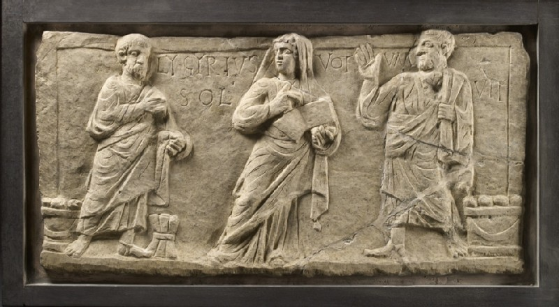 Marble relief with a woman holding an open scroll between two men with Latin inscription Lygyrius fulfilled his vow