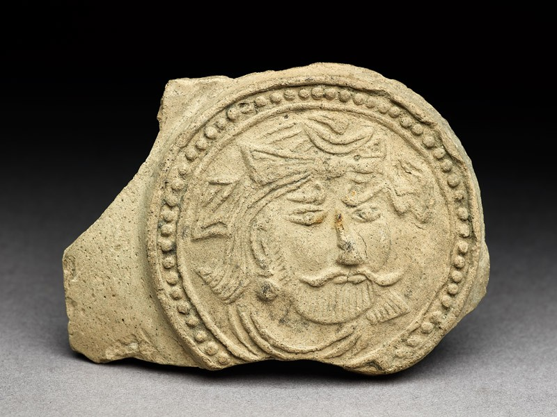 Medallion from a pot depicting a bearded figure, possibly a bodhisattva