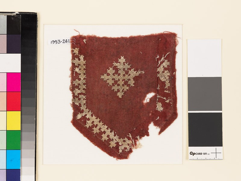 Textile fragment from a tab with a cross, shield-shape, and linked crosses (EA1993.241, front            )